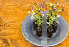 Gray Plate With Vases och blommor på tabellen Royaltyfria Foton