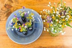 Gray Plate With Vases och blommor på tabellen Royaltyfria Bilder
