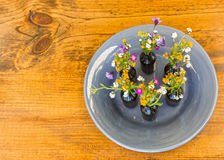 Gray Plate With Vases und Blumen auf Tabelle Stockfoto
