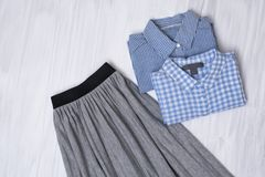 Gray pleated skirt and blue shirts on wooden background. Fashion. Able concept royalty free stock photography