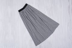 Gray pleated skirt on wooden background. Fashionable concept.  stock image