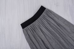 Gray pleated skirt on wooden background. Fashionable concept. Cl. Ose up stock photo