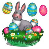 Gray plush bunny lies on grass mat with colored painted Easter eggs.  Royalty Free Stock Photos