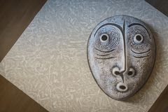 Gray porcelain mask on a gray background. Mask with surprised emotion stock photos