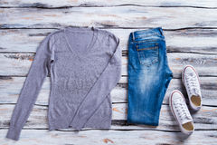 Gray pullover and blue jeans. Sweatshirt, jeans and keds. Casual apparel and footwear. Simple clothes on white floor Royalty Free Stock Images