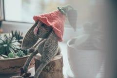 Gray Rabbit Amigurumi Plush Toy on Wood Trunk Stock Images