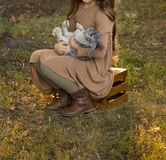 A gray rabbit sits on the girl in her arms, sitting on a glade with green grass on a wooden box. Brown hair and brown dress. the g royalty free stock photo