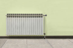 Gray radiator on a yellow wall Royalty Free Stock Photo