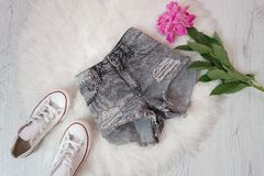 Gray ragged shorts, white sneakers and peony flower. Fashionable concept, white fur on the background.  Royalty Free Stock Images