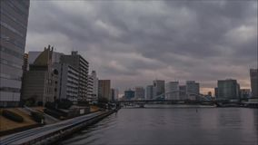 Gray rain clouds moving in fast time lapse dark sky over Tokyo city downtown financial district architecture by river