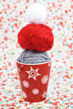 Gray, red and white ball for knitting and red Christmas cup on the background Royalty Free Stock Image