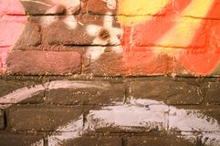 A gray, red, yellow and white brick wall painted with paint. Texture. The background Royalty Free Stock Photo