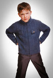 Gray restless evil angry kid gloomy blond boy in striped sweater Royalty Free Stock Images