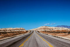 Gray Road Beside Brown Dessert Under Blue Sky Royalty Free Stock Images