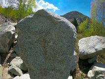Gray rock, high mountain, blue sky in high contrast. Gray rock in front of mountain and blue sky. Shoot was taken in early May. HDRI compilation Royalty Free Stock Image
