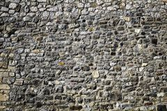 Gray rocky wall of castle. Grey rocky wall of old medieval castle, different sizes of rocky stone bricks royalty free stock photography