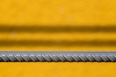 Gray rod of fittings on a yellow background Royalty Free Stock Photography