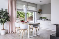 Gray roman shades and a pink curtain on big, glass windows in a. Modern kitchen and dining room interior with a wooden table and white chairs stock photos