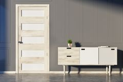 Gray room, chest of drawers and door. Gray living room interior with a chest of drawers, a potted plant and several book on it and a white and wooden door. 3d Royalty Free Stock Photo