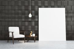 Gray room with a white armchair and a poster. Empty gray room interior with a white armchair standing on a concrete floor near a coffee table with a wooden cat Royalty Free Stock Image