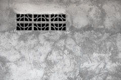 Gray rough concrete wall with ventilation window Stock Image