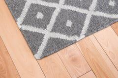 Gray rug on wooden floor Stock Photos
