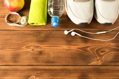 Gray running shoes and fitness accessories on wooden background. Empty text space royalty free stock image