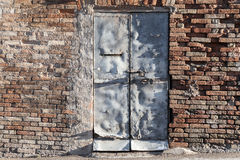 Gray rusted metal door in old brick wall, background Stock Images