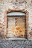 Gray rusted metal gate in old brick wall, background Royalty Free Stock Image