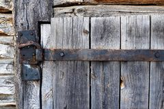 Rusty aged iron hinge on old wooden door royalty free stock images