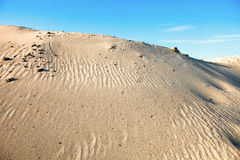 Gray sand dunes and the blue sky Royalty Free Stock Photo