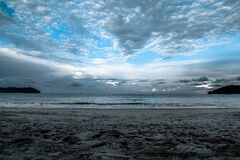 Gray Sand on Sea Shore Under Cloudy Sky during Daytime Stock Photography