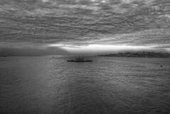 Gray Scale Photo of a Boat on Body of Water Under Cloudy Sky Royalty Free Stock Images