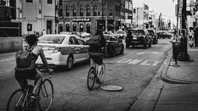 Gray Scale Photo Person Riding on the Bicycle Near White Taxi Car in the Cityblack and White Photo of City Street With Cars and Bi Royalty Free Stock Images