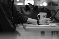 Gray Scale Photograph of Person Sitting Beside Black Leather Bag stock photo