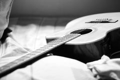 Gray Scale Photography of Acoustic Guitar on Bed Stock Photos
