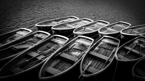 Gray Scale Photography of Wooden Rowboats on Body of Water Royalty Free Stock Photos