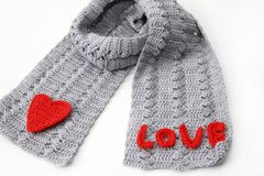 Gray scarf with red crocheted heart. On white background Royalty Free Stock Photos