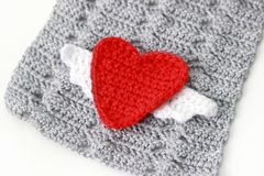 Gray scarf with red crocheted heart. On white background Stock Images