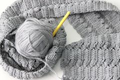 Gray scarf with thread and hook. Gray scarf with thread and yellow hook Royalty Free Stock Photography
