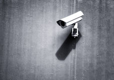 Gray security camera with shadow. Grunge gray security camera with shadow on the public cement concrete wall background Royalty Free Stock Photography