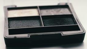 Gray shades of eyeshadow,Close up of makeup brush moving over eye shadows stock video
