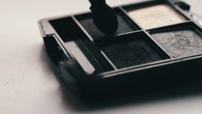 Gray shades of eyeshadow,Close up of makeup brush moving over eye shadows stock footage