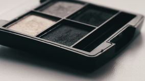 Gray shades of eyeshadow,Close up of makeup brush moving over eye shadows stock video footage