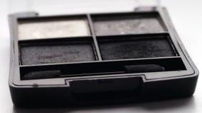 Gray shades of eyeshadow,Close up of makeup Eyebrow brush moving over eye shadows stock video