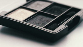 Gray shades of eyeshadow,Close up of makeup Eyebrow brush moving over eye shadows stock video footage