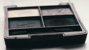 Gray shades of eyeshadow,Close up of makeup Eyebrow brush moving over eye shadows. Close up of makeup Eyebrow brush moving over eye shadows.Gray shades of stock footage