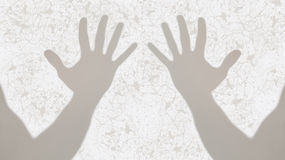 Gray shadows of two open hands on white inky background Stock Photo