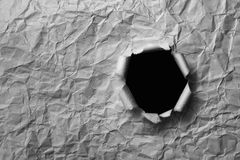 Gray sheet ofcrumpled paper with a hole Stock Images