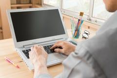 Gray Shirt Businessman Typing Laptop of Notitieboekje in Huisbureau royalty-vrije stock foto's